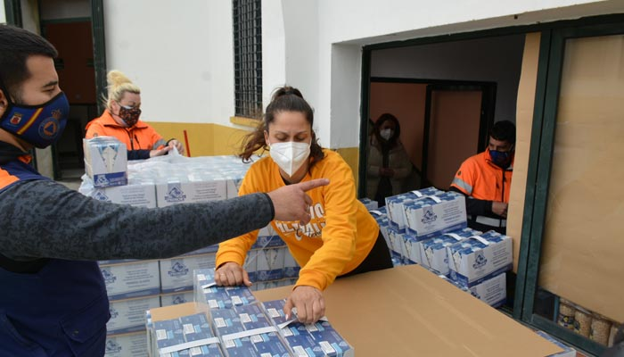 Descarga de los alimentos por parte de voluntarios de Protección Civil