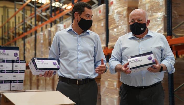 Juanma Moreno y Jesús Aguirre en una imagen reciente recibiendo muestras de tests rápidos
