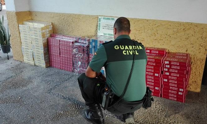 Un agente de la Guardia Civil junto a un cargamento de tabaco de contrabando