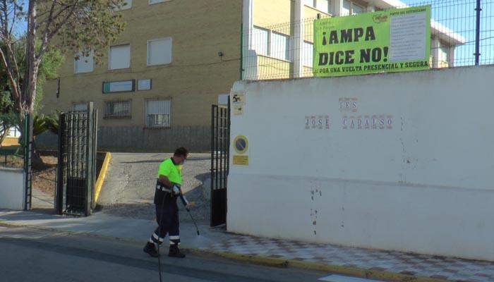 Un operario desinfectando en la entrada del IES José Cadalso