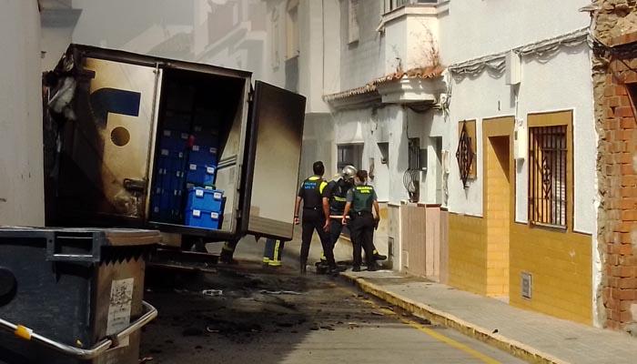 El camión siniestrado y bomberos accediendo a la vivienda de un matrimonio mayor
