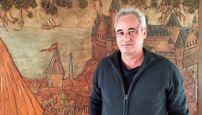 El artista junto a un relieve de su autoría