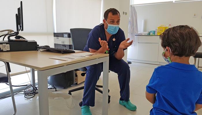 Uno de los pediatras del Hospital Quirónsalud con un joven paciente