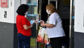 Una empleada municipal entregando las mascarillas