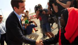 Pablo Casado saluda a uno de los migrantes