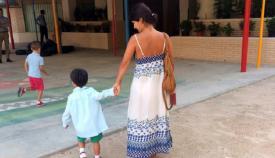 Una madre acompaña a su hijo en el primer día de colegio del nuevo curso