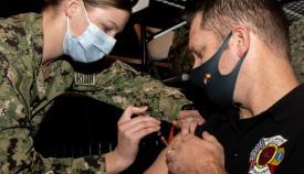 Un miembro de los equipos contra incendios de la base, recibe la vacuna contra la COVID. Foto US Navy