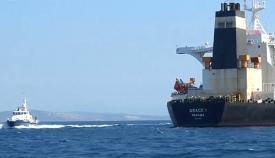Una patrullera de la RGP pasa cerca del Grace One, fondeado cerca de Gibraltar