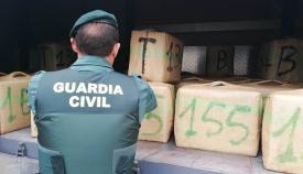 Un agente de la Guardia Civil junto a un cargamento de hachís