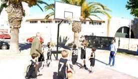 El alcalde observa a los niños jugar a baloncesto en la nueva canasta