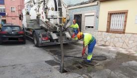 Operarios municipales limpiando imbornales en la calle Lepanto