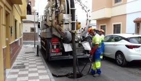 Operarios municipales limpiando imbornales en una calle de La Línea