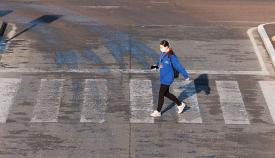 Una mujer con mascarilla cruzando un paso de peatones. Foto Sergio Rodríguez
