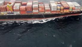 En la foto se aprecia la patera a escasos metros del enorme buque