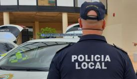 Un agente de la Policía Local de La Línea junto a un vehículo del cuerpo