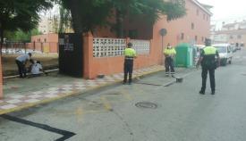 Agentes de la Policía Local y operarios municipales junto a un colegio linense