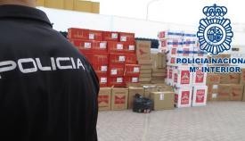 Un agente de la Policía Nacional junto a un cargamento de trabaco ilícito