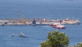 Los prácticos maniobra con el USS Olympia al salir hoy del puerto de Gibraltar